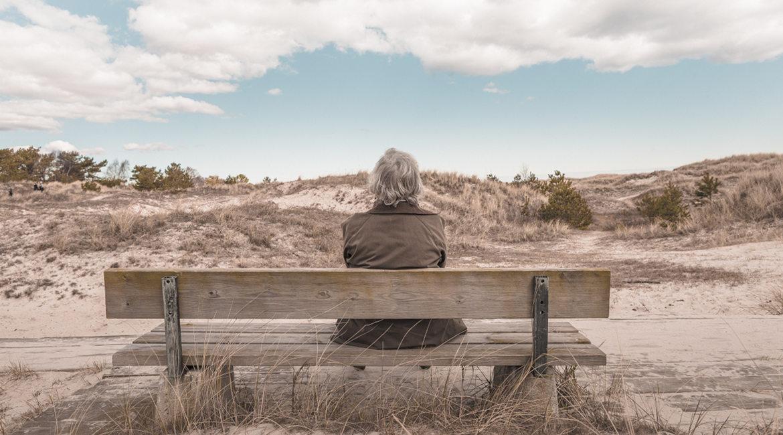 Bild eines Mannes auf einer Bank am Strand