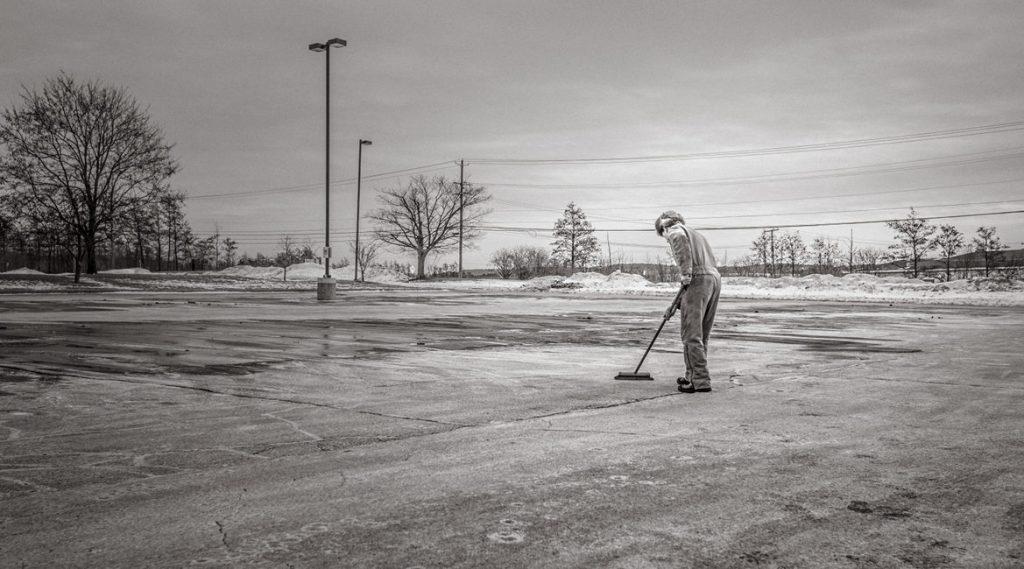 Bild eines Mannes, der eine Straße fegt
