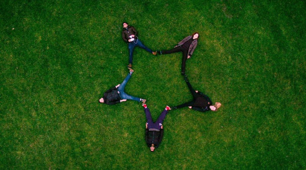 Bild fünf junger Menschen, die einen Stern formen