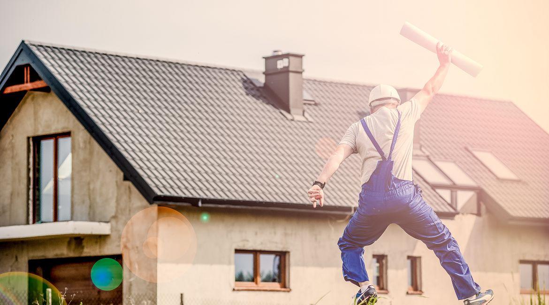 Bild eines Bauarbeiters vor einem Haus
