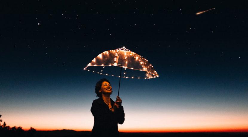 Frau mit Regenschirm unter Sternenhimmel