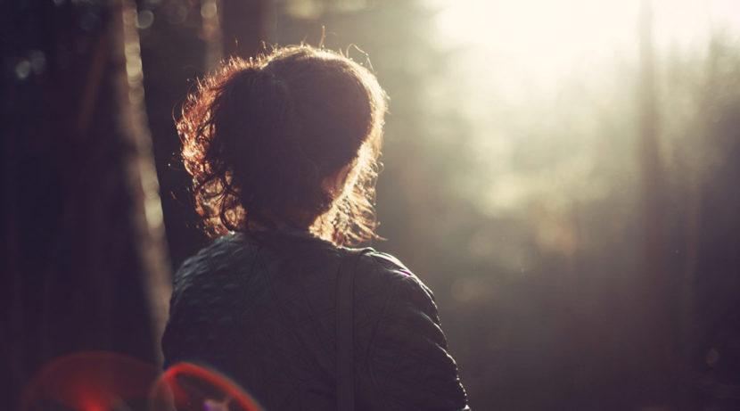 Bild einer sitzenden Frau im Wald